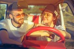 坐在汽车的笑的浪漫夫妇,当在旅行夏日时 免版税库存照片