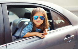 坐在汽车的美丽的小女孩孩子,看窗口 免版税库存照片