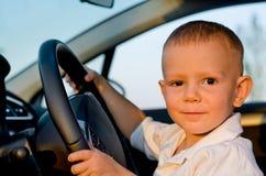 坐在汽车的轮子的之后小男孩 免版税库存照片
