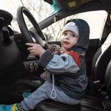 坐在汽车的轮子的之后小男孩 免版税图库摄影