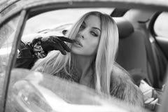 坐在汽车的Portret美丽的白肤金发的妇女 免版税图库摄影