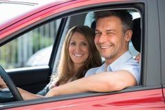 坐在汽车里面的夫妇 免版税库存图片