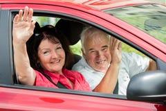 坐在汽车里面的愉快的资深夫妇 库存照片