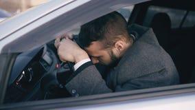 坐在汽车非常生气和被注重在硬失效以后和移动交通堵塞的年轻有胡子的商人 股票录像