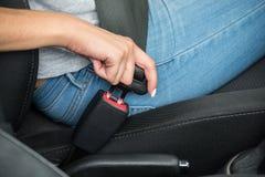 坐在汽车紧固安全带里面的女性` s手 库存照片