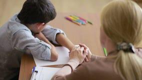 坐在沈默的男孩在与握手的年轻心理学家的会议期间 股票视频