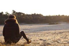 坐在沙丘的妇女 免版税库存照片