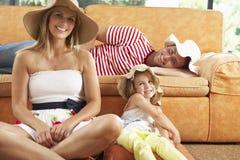 坐在沙发佩带的草帽前面的家庭 免版税库存照片