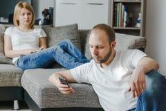 坐在沙发的少妇谈话与她的丈夫,当他在他们的客厅时使用他的手机 库存照片