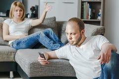 坐在沙发的恼怒的少妇谈话与她的丈夫,当他在他们的客厅时使用他的手机 库存照片