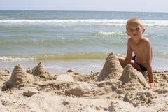 坐在沙子城堡旁边的男孩 库存图片