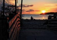 坐在沙子的人剪影观看在天际的深刻的橙色日落在马拉松钥匙的阔边帽海滩 免版税库存照片