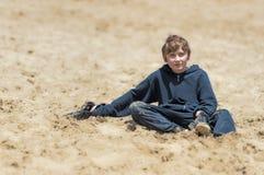坐在沙子的男孩看照相机 库存照片