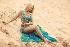 坐在沙子的肚皮舞表演者妇女 库存图片