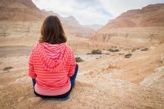 坐在沙漠谷上的妇女 免版税库存照片