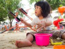坐在沙盒和使用与玩具沙子铁锹桶和她的一点亚洲女孩挖出在玩具铁锹桶的沙子 库存照片