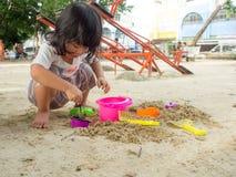 坐在沙盒和演奏丝毫玩具铁锹桶和她的一点亚洲女孩在玩具铁锹桶挖出 免版税库存图片
