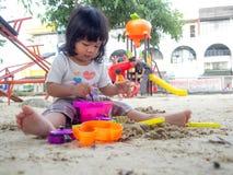 坐在沙盒和演奏丝毫玩具铁锹桶和她的一点亚洲女孩在玩具铁锹桶挖出 库存照片