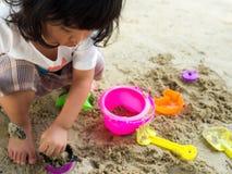 坐在沙盒和演奏丝毫玩具铁锹桶的一点亚洲女孩 免版税库存照片