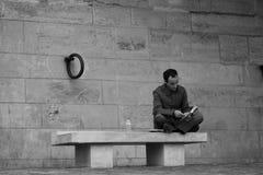 坐在河塞纳河的江边的一条长凳和读书的一个人 免版税库存图片