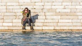 坐在河岸的女孩 免版税图库摄影