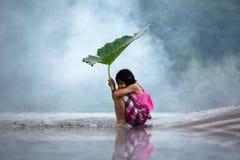 坐在河沿的小女孩是哀伤的感觉 免版税库存照片
