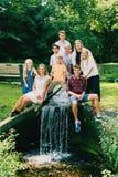 坐在河的快乐的兄弟姐妹或朋友 库存照片