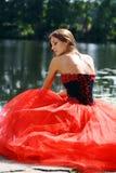 坐在河附近的一件红色礼服的哀伤的妇女 免版税库存图片