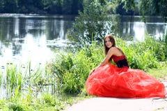 坐在河附近的一件红色礼服的妇女 免版税库存照片