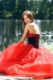 坐在河附近的一件红色礼服的妇女 库存照片