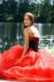 坐在河附近的一件红色礼服的妇女 图库摄影