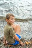 坐在河附近的严肃的小男孩特写镜头画象  免版税图库摄影
