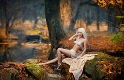 坐在河附近的可爱的小姐在被迷惑的森林 有诱惑摆在秋季公园的白色衣裳的肉欲的金发碧眼的女人 库存照片