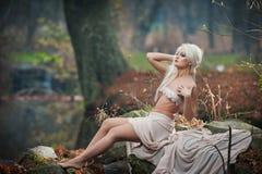 坐在河附近的可爱的小姐在被迷惑的森林 有诱惑摆在秋季公园的白色衣裳的肉欲的金发碧眼的女人 图库摄影