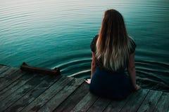 坐在沼泽湖fornt的孤独的女孩  免版税库存照片