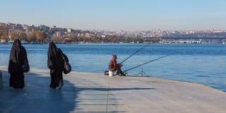 坐在沿海岸区散步和穆斯林的渔夫穿戴了夫人走 免版税库存照片
