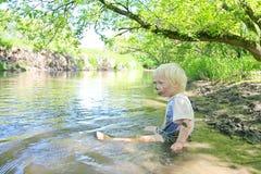 坐在泥泞的河的男婴在森林里 库存照片