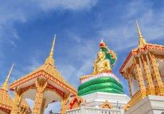 坐在泰国寺庙的绿色泰国龙雕象下的大金黄菩萨雕象 库存照片