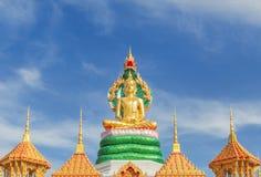 坐在泰国寺庙的绿色泰国龙雕象下的大金黄菩萨雕象 免版税库存图片