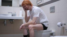 坐在洗手间,洗脸台的时态生气红头发人人 图库摄影