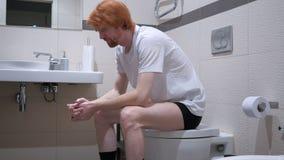 坐在洗手间,洗脸台的紧张的红头发人人 免版税库存照片
