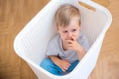 坐在洗衣篮和使用的两岁的男孩 免版税图库摄影