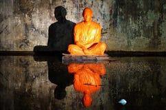 坐在洞的橙色修士雕象 免版税图库摄影