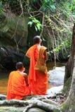 坐在流或瀑布附近的修士在密林 免版税库存照片
