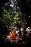 坐在流或瀑布附近的修士在密林 免版税库存图片