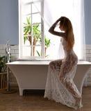 坐在浴缸附近的年轻美丽的妇女准备好洗浴近 免版税图库摄影