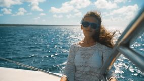 坐在海中的游艇边缘的太阳镜的女孩 股票视频