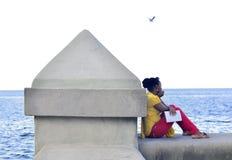 坐在海前面的一个美丽的女孩 免版税库存照片