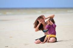 坐在海夏天的母亲和女儿 免版税库存图片