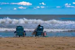 坐在海洋的边缘的人们 库存照片
